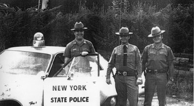 Left to right - Trooper Denny McGuire, Trooper Preston Piasecki, and Trooper Jeff Hagadorn stand outside of SP Rhinebeck in 1975